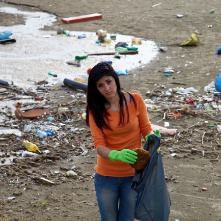 Unhappy girl cleaning destroyed beach by pollution