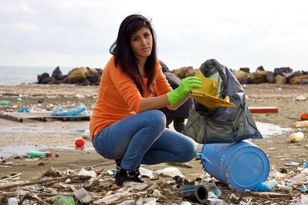 Mujer triste recogiendo volcado en la playa sucia