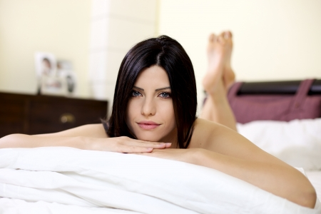 lying in bed: Woman relaxing in bed smiling happy