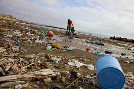 Depressief meisje oppakken met een zak vuile op het strand in Middellandse Zee