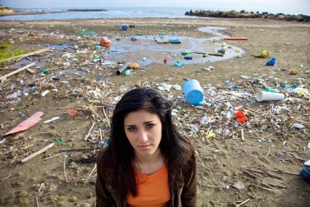 Portret van depressieve vrouw staande voor afval en recycle vuile strand