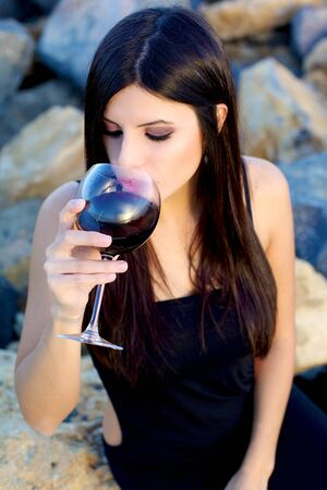 sea sexy: Beautiful woman with night dress sitting on rocks smelling red wine