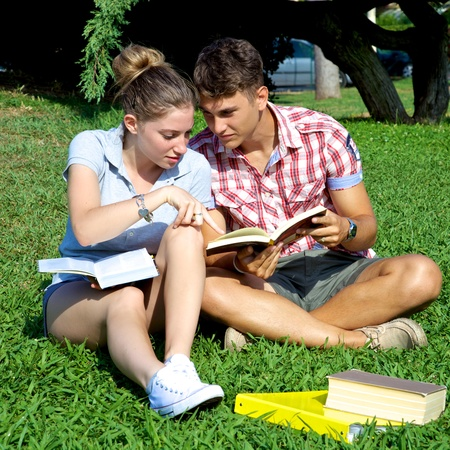 Handsome boy and gorgeous girl sitting on grass studying books in college photo