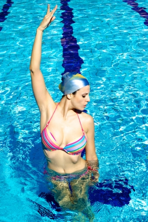 Good looking female model in water exercizing synchronized swim photo