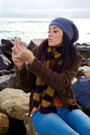Young woman with scarf and hat taking picture of herself with iphone photo