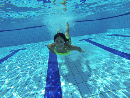 Gorgeous caucasian young woman swimming underwater
