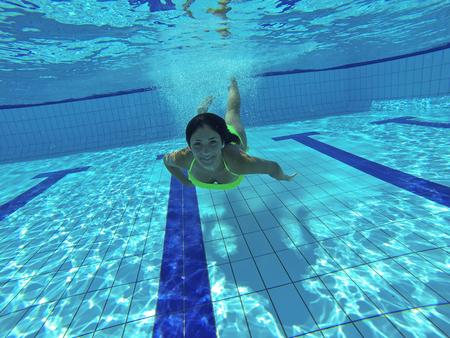 Prachtige Kaukasische jonge vrouw zwemmen onder water Stockfoto