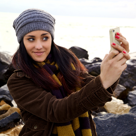 Gorgeous young woman taking picture with mobile phone photo