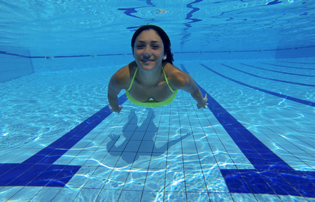 Smiling girl underwater in swimmingpool photo