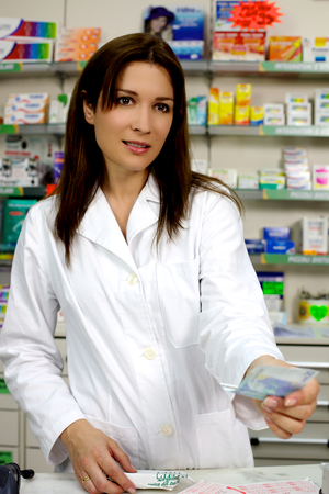Smiling female pharmacist at counter with euros photo