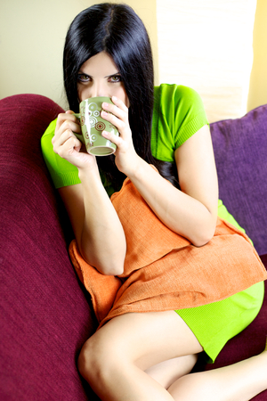 Smiling beautiful woman with long dark hair drinking at home coffee photo