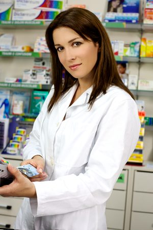 Smiling pharmacist woman at counter with credit card photo
