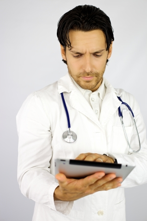 Serious doctor researching treatment with tablet photo