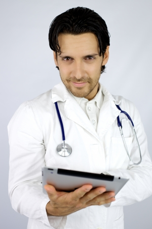 Handsome doctor smiling with tablet in hand photo