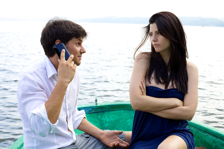 pareja discutiendo: Mujer celosa de su novio en el teléfono hablando y sonriendo