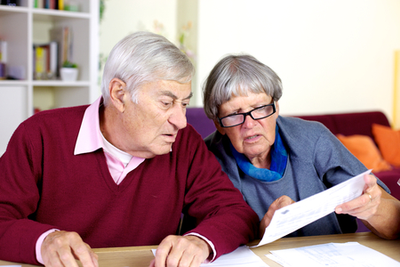 Elder couple looking at documents on the table in the living room photo