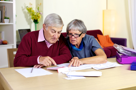 Senior couple at home reading documents and bills photo