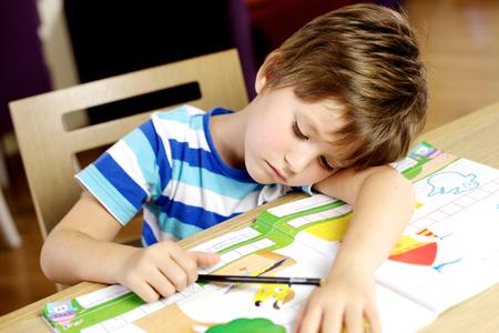 Hermoso niño caucásico rubio durmiendo mientras se dibuja en la mesa