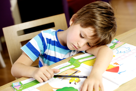 Beautiful blond caucasian child sleeping while drawing on the table Stockfoto