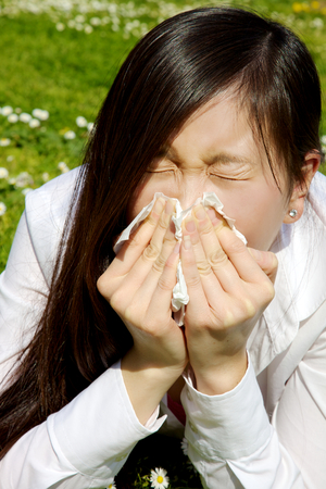 Sic asian woman sneezing in park photo