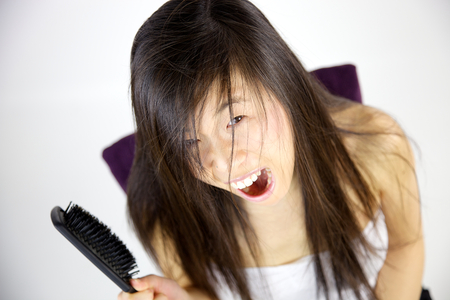 Angry asian woman hating her long messy hair photo