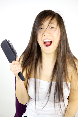 Cute asian girl in trouble with long hair not able to comb it photo
