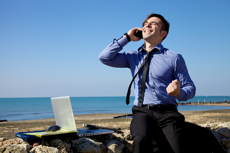 telephone salesman: Happy handsome man talking business deal went well