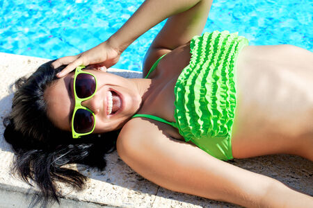 Happy young woman with green bikini and sunglasses photo