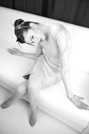 Beautiful woman sitting in strange position on white sofa photo