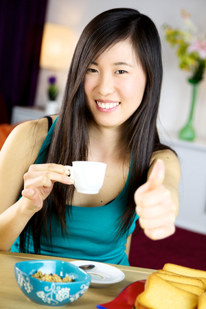 Happy gorgeous Chinese American girl drinking coffee espresso photo