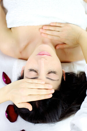 Woman laying in spa with hands of professional therapist on head photo