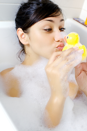 Happy young woman having fun with duck toy photo