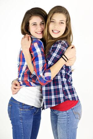 two women hugging: Smiling girls in studio hugging showing friendship Stock Photo