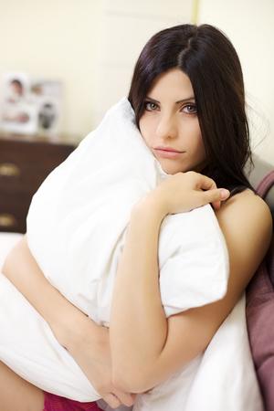 decepción: retrato de una mujer joven, triste, deprimido y solitario abrazando una almohada que se sienta en la cama en su casa Foto de archivo