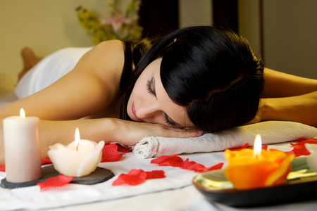pretty brunette woman relaxing on massage table with candles at spa with eyes closed photo