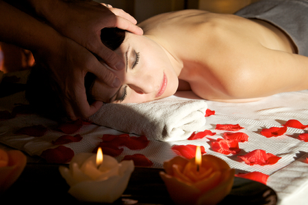 attractive female getting recreation massage of head with closewd eyes at spa salon photo