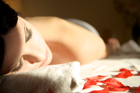 Beautiful brunette woman relaxing on massage table at a luxury spa with eyes closed photo