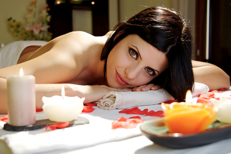 beautiful woman relaxing at spa salon lying on a spa  table with candles photo
