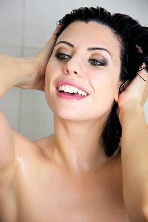 Young woman in spa washing her head in the shower photo
