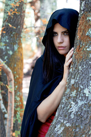 portrait of attractive woman vampire hiding behind a tree in the woods ready to attack photo