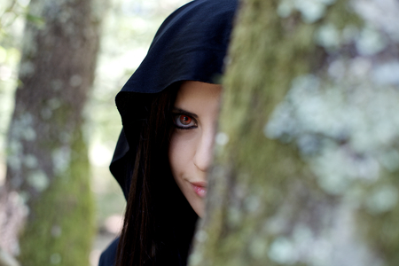 vampire girl: beautiful vampire woman hidden behind a tree in the forest Stock Photo