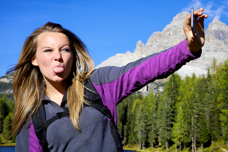 beautiful funny young woman doing a bigmouth for a selfie photo in mountain Archivio Fotografico