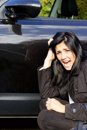 Unhappy woman about scratch on new car Stock Photo