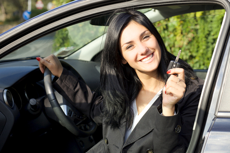 Cute young woman happy about new car photo