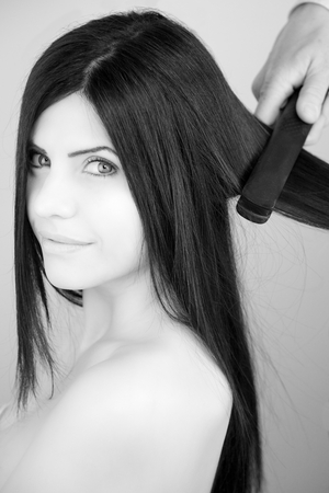 Beautiful woman smiling while stylist is straightening long black hair photo