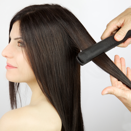 Long hair being straightened with iron by stylist photo