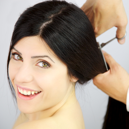 hair stylist: Hair stylist cutting long hair with scissors
