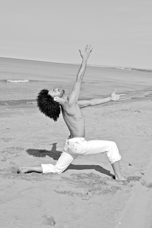 beach hunk: Cool man with curly hair having fun on the beach black and white
