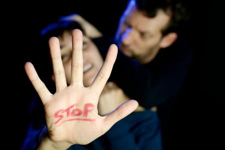 violencia intrafamiliar: Hombre estrangula mujer joven con se�al de stop en la mano Foto de archivo