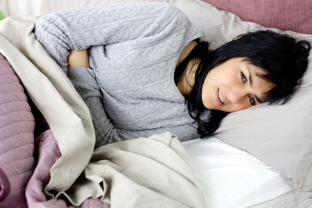 stomachache woman: Woman feeling sick in bedroom